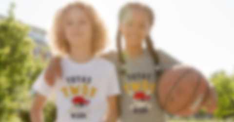 Dwoje dzieci pozuje w samodzielnie zaprojektowanych koszulka podczas gry w koszykówkę