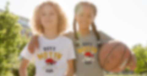 Två barn poserar i egendesignade T-shirts när de spelar basket