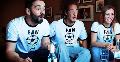 Troje przyjaciół ogląda mecz piłki nożnej w samodzielnie zaprojektowanych koszulkach kibica z nadrukiem wykonanym przez Spreadshirt.