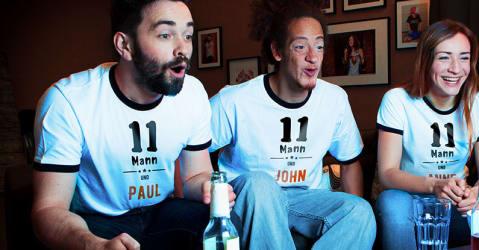 Drei Freunde schauen Fußball in selbst gestalteten Fan-T-Shirts, die von Spreadshirt bedruckt wurden.