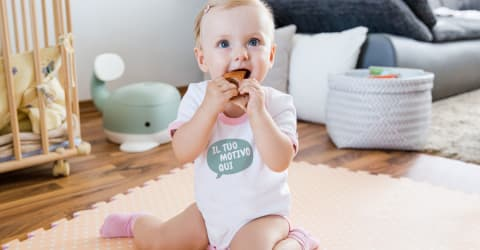 cce62c7512 Bimba che sorride mentre gioca in soggiorno e indossa un body  personalizzato per neonato.