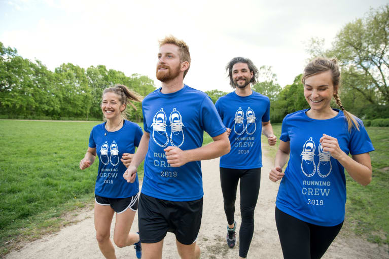 Men and women running team wearing customised gear with text