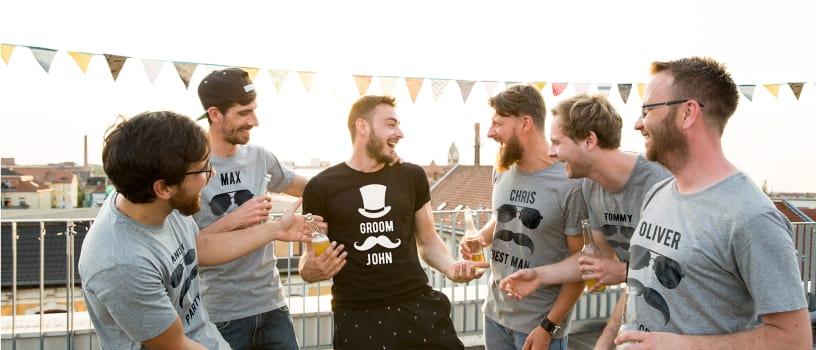 Amici che festeggiano un addio al celibato indossando magliette da loro create