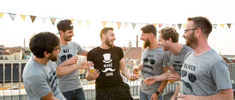 Un groupe d'amis réuni pour fêter un enterrement de vie de garçon avec des t-shirts EVG personnalisés.