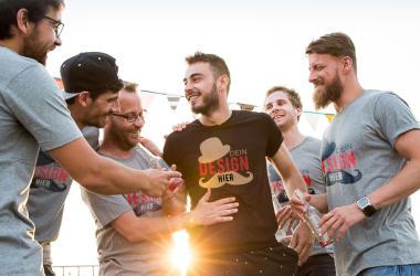 Freunde tragen selbst gestalte T-Shirts mit personalisiertem Text zum Junggesellenabschied