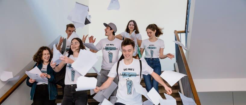 Schüler feiern ihren Schulabschluss und tragen selbstgestaltete Abi T-Shirts