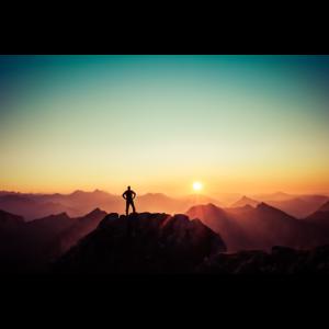 Mann auf Berggipfel bei Sonnenuntergang
