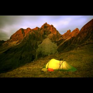 Zelt leuchtet bei Nacht in den Bergen