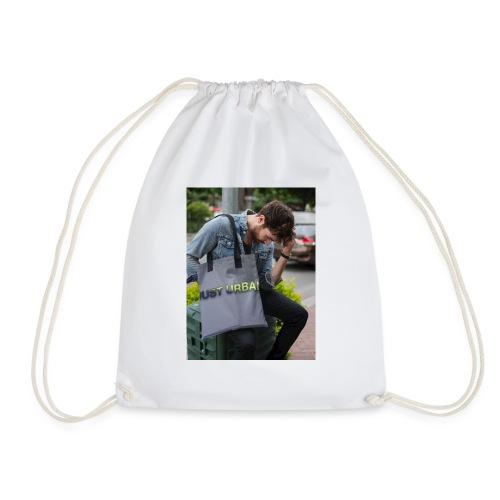man carrying a tote bag mockup while looking to th - Drawstring Bag